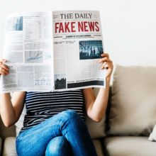 Woman reading newspaper with headline: fake news