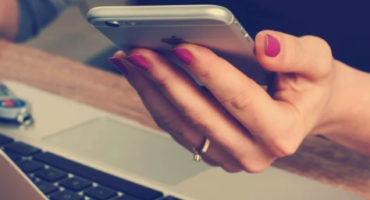 lady's hand hold phone whilst sitting at laptop