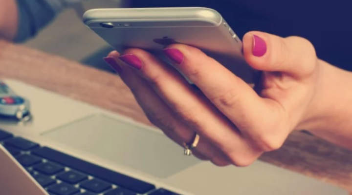 hand holding a mobile phone in front of a computer